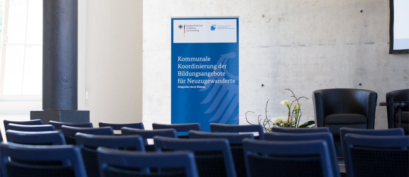 Das Bild zeigt das in einem Konferenzraum neben dem Podium aufgestellte Poster der Fachveranstaltung für kommunale Koordinatorinnen und Koordinatoren mit der Aufrschift Kommunale Koordinierung der Bildungsanegebote für Neuzugewanderte.
